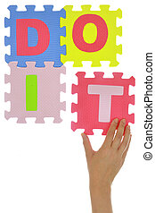 "Hand forming phrase ""Do it"" made with jigsaw puzzle pieces"