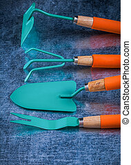 Hand gardening tools with wooden handles on scratched metallic b
