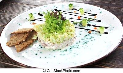 Hand garnishing food close up. Herring tartare on a plate.