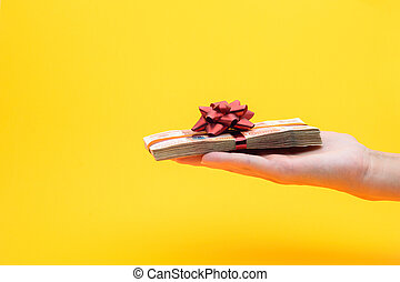 Hand gives a pack of five thousandth bills on a yellow background