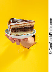 Hand giving a piece of cake through a torn hole in yellow paper background.