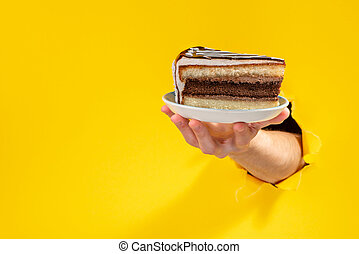 Hand giving a piece of chocolate cake through a torn hole in yellow paper background.