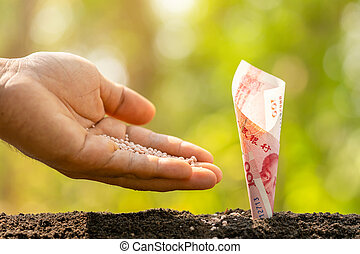 Hand giving fertilizer to Chinese banknote (100 Yuan) ...