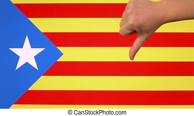 Hand giving thumb down with Catalonia flag disapproval gesture with copy space