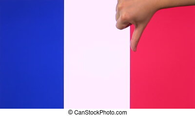 Hand giving thumb down with France flag disapproval gesture with copy space