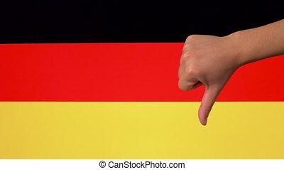 Hand giving thumb down with Germany flag disapproval gesture...