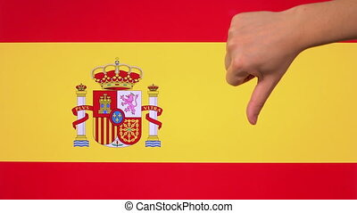 Hand giving thumb down with Spain flag disapproval gesture with copy space