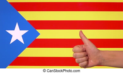 Hand giving thumb up with Catalonia flag, approval gesture with copy space
