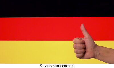 Hand giving thumb up with Germany flag, approval gesture with copy space