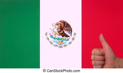 Hand giving thumb up with Mexico flag, approval gesture with copy space
