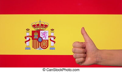 Hand giving thumb up with Spain flag, approval gesture with copy space