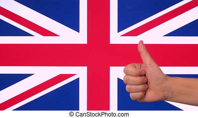 Hand giving thumb up with United Kingdom flag, approval gesture with copy space