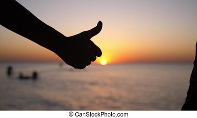 Hand giving thumbs up at sunset background on the beach