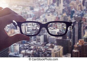 Hand glasses cityscape - cityscape focused in glasses lenses...