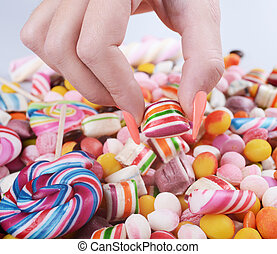 Hand grabbing candy from pile - Overweight problem concept