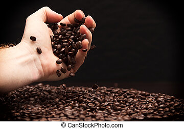 Hand grabbing coffee beans. - High contrast image of hand...