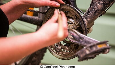 Hand greases the bicycle sprocket - The hand, with the help...