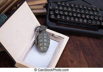 hand grenade hidden in a book with old retro typewriter