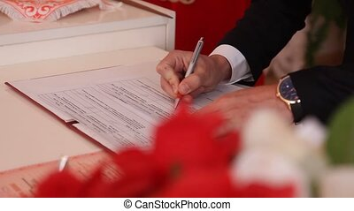 hand groom puts the signature on the wedding ceremony
