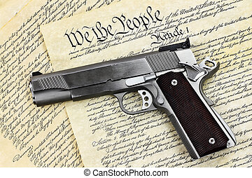 Hand Gun and Constitution - Handgun lying over a copy of the...