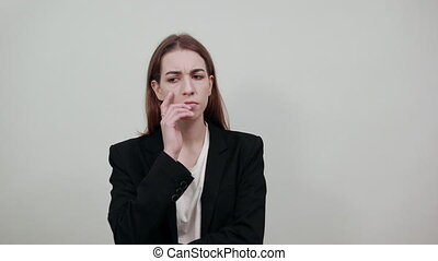Hand on head thinking about question, pensive expression. Doubt. Thoughtful face. Using that incredibly sharp business mind. Young attractive woman with brown hair in a light t-shirt and black jacket