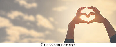 Hand heart shape silhouette made against the sun and sky of a sunrise or sunset.