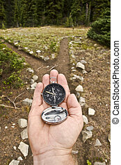 Hand Held compass at Trail Junction - A traditional magnetic...
