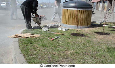 hand held electric saw - worker carefully cut small cement...