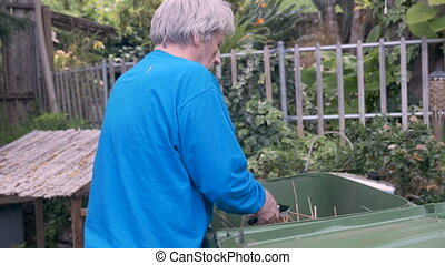 Hand held of an elderly man rubbing his back while working in the yard