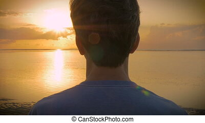 Hand held over the shoulder of man watching sunset over the ocean