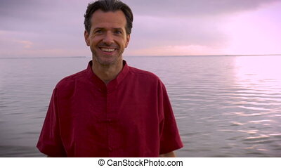 Hand held puch-in shot of middle aged man smiling at the camera with sunrise