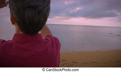 Hand held shot of a middle aged man taking photos of a sunrise on the beach