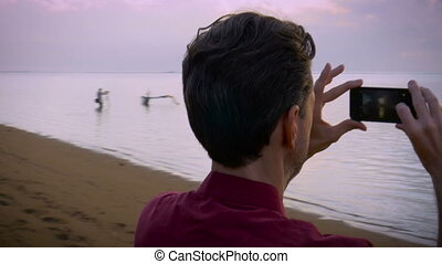 Hand held shot of a middle aged man taking smart phone photos on the beach