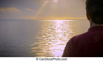 Hand held shot of man walking into the light in water of a calm sea
