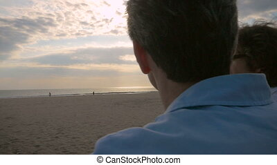 Hand held shot of two men talking and watching the sunset...