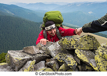 Hand helping hiker to climb the mountain