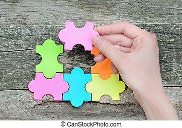 hand hold a paper puzzle on table