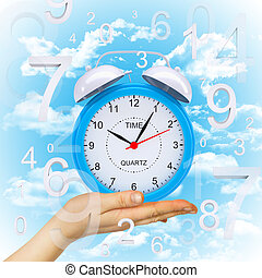 Hand hold alarm clock with figures. Blue sky background