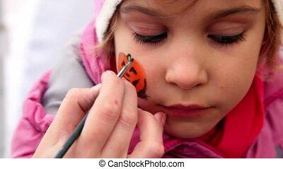 Hand hold brush and draw pumpkin on girls cheek, closeup...