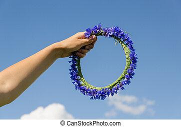 hand hold cornflower crown in blue sky background