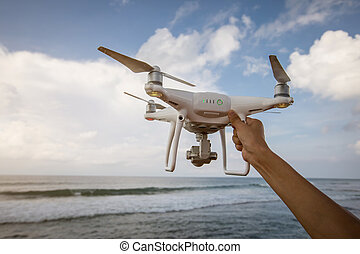 Hand hold drone on seaside