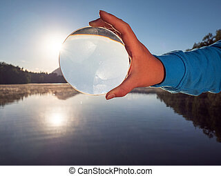 Hand hold glass lens or ball uniquely reflects world