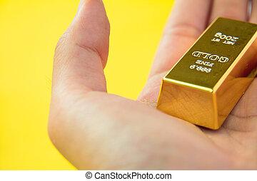 Hand hold gold bar