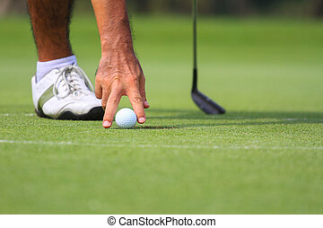 Hand hold golf ball on course