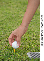 Hand hold golf ball with tee on course, close-up