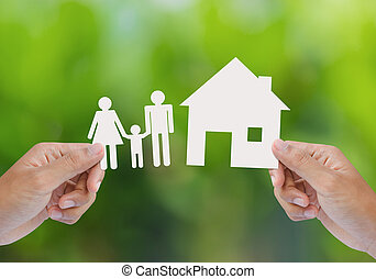 Hand hold house and family on green