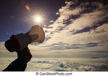 hand hold loudspeaker to sky on mountain peak
