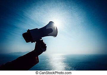 Hand hold megaphone against sea under sky background