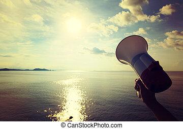 Hand hold megaphone with sunrise sea