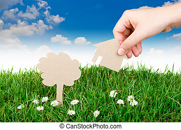 Hand hold paper cut  of House over  fresh spring green grass